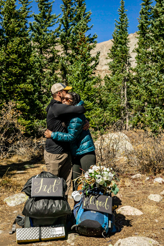 A newly married couple hugging with their Just Eloped sign, DIY wedding sign, strapped onto a backpack. Photo by Gabby Jockers Photography. Colorado elopement ideas, elopement inspiration, elopement ideas, Colorado elopement photographer, Colorado elopement photography, hiking elopement, backpacking elopement, Rocky Mountain national park wedding, rocky mountains, backpacking wedding, camping wedding, fall wedding, adventure wedding, adventurous elopement, mountain elopement, elopement with dog, dog of honor, best dog