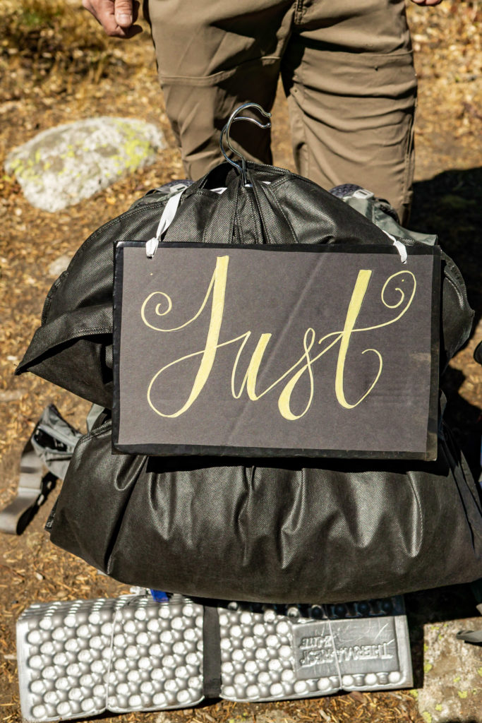 Just Eloped sign, DIY wedding sign, strapped onto a backpack. Photo by Gabby Jockers Photography. Colorado elopement ideas, elopement inspiration, elopement ideas, Colorado elopement photographer, Colorado elopement photography, hiking elopement, backpacking elopement, Rocky Mountain national park wedding, rocky mountains, backpacking wedding, camping wedding, fall wedding, adventure wedding, adventurous elopement, mountain elopement, elopement with dog, dog of honor, best dog