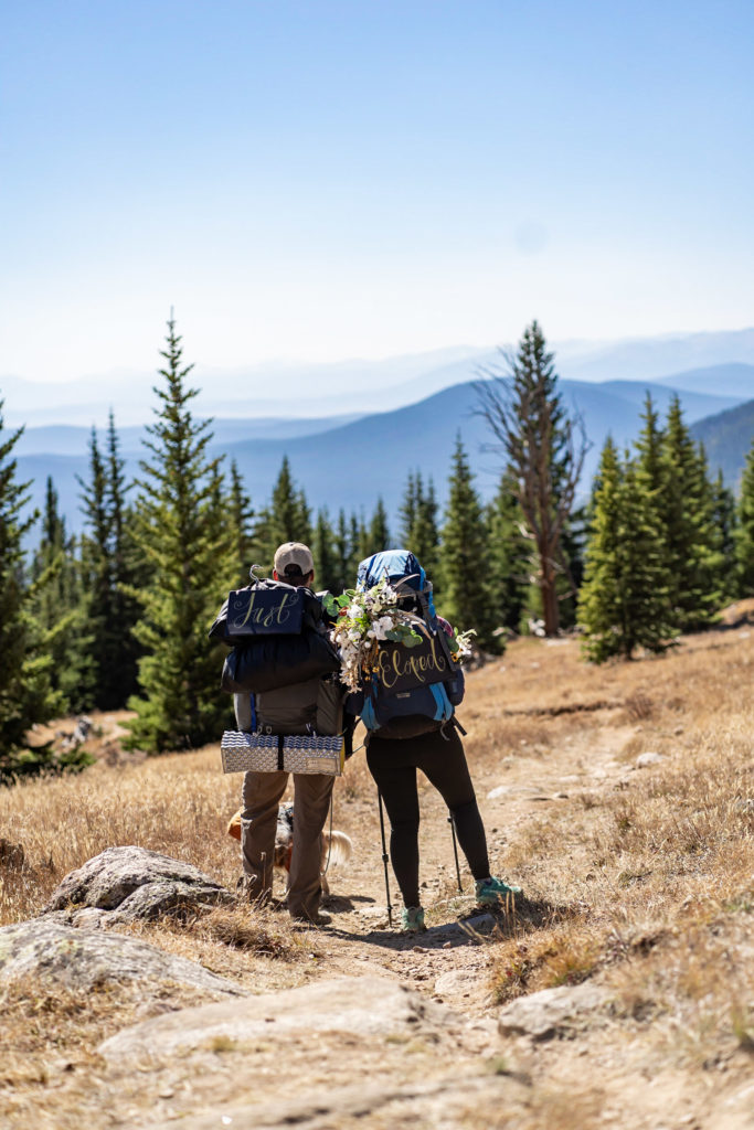 """A newly married couple standing next to each other looking over the view with """"Just Married"""" backpack signs. Photo by Gabby Jockers Photography. Colorado elopement ideas, elopement inspiration, elopement ideas, Colorado elopement photographer, Colorado elopement photography, hiking elopement, backpacking elopement, Rocky Mountain national park wedding, rocky mountains, backpacking wedding, camping wedding, fall wedding, adventure wedding, adventurous elopement, mountain elopement, elopement with dog, dog of honor, best dog"""