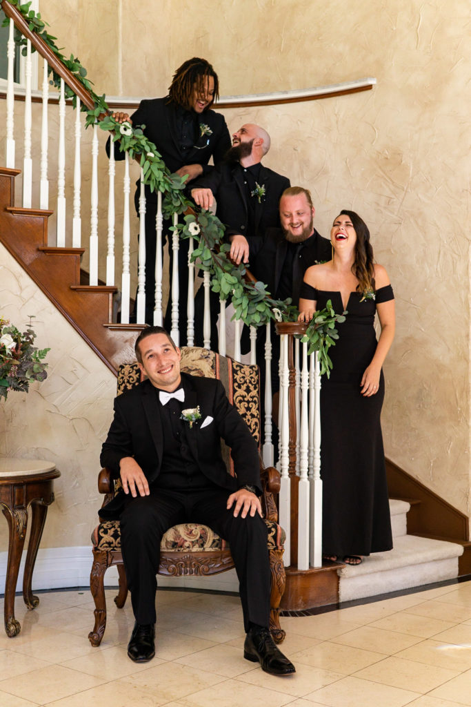 A groom with his groomsmen and best woman posed along a staircase and laughing together. Photo by Gabby Jockers Photography. Garden of the Gods wedding, High point wedding, Colorado intimate wedding, Colorado elopement ideas, elopement inspiration, elopement ideas, Colorado elopement photographer, intimate wedding photography, Rocky Mountain national park wedding, rocky mountains, intimate wedding, September wedding, mountain ceremony view, red rocks wedding