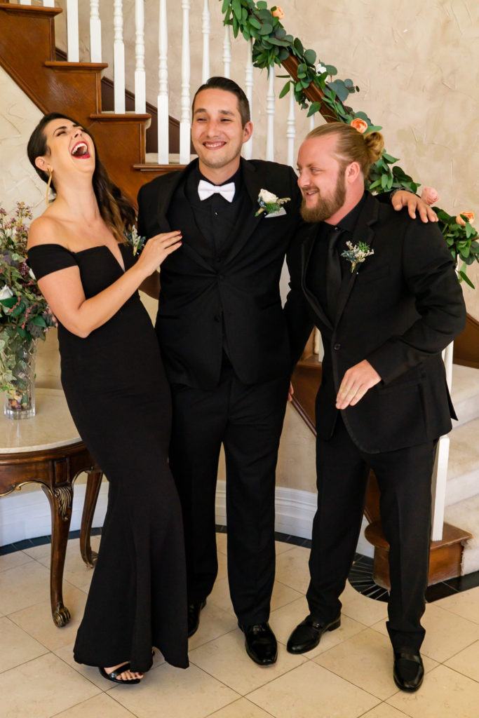 A groom standing and laughing with his best man and best women, all wearing black. Photo by Gabby Jockers Photography. Garden of the Gods wedding, High point wedding, Colorado intimate wedding, Colorado elopement ideas, elopement inspiration, elopement ideas, Colorado elopement photographer, intimate wedding photography, Rocky Mountain national park wedding, rocky mountains, intimate wedding, September wedding, mountain ceremony view, red rocks wedding