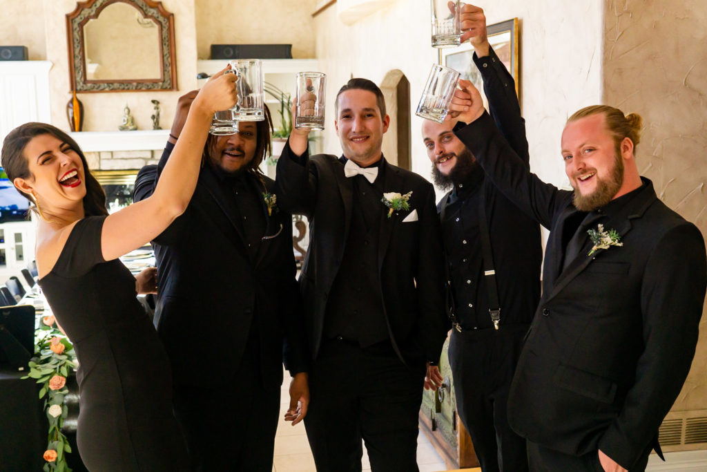 The wedding party and groom wearing all black and toasting merrily with giant cups. Photo by Gabby Jockers Photography. Garden of the Gods wedding, High point wedding, Colorado intimate wedding, Colorado elopement ideas, elopement inspiration, elopement ideas, Colorado elopement photographer, intimate wedding photography, Rocky Mountain national park wedding, rocky mountains, intimate wedding, September wedding, mountain ceremony view, red rocks wedding