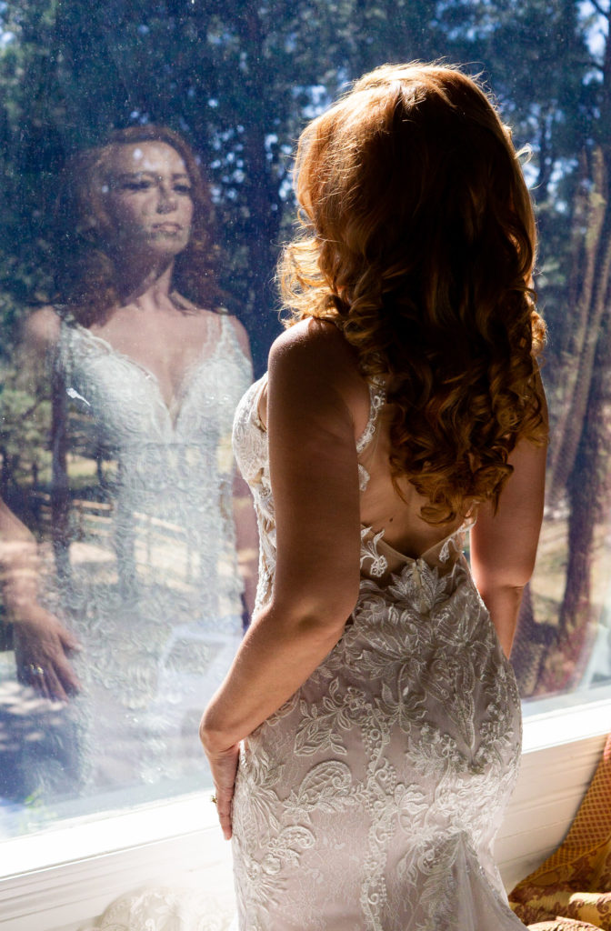 A bride wearing a low back lace dress in front of a mirror. Photo by Gabby Jockers Photography. Garden of the Gods wedding, High point wedding, Colorado intimate wedding, Colorado elopement ideas, elopement inspiration, elopement ideas, Colorado elopement photographer, intimate wedding photography, Rocky Mountain national park wedding, rocky mountains, intimate wedding, September wedding, mountain ceremony view, red rocks wedding
