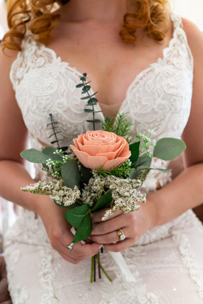 A close up details shot of the bride with her curly red hair holding a small wood bouquet with salmon colored flowers , an antique gold engagement ring, and an heirloom ring. Photo by Gabby Jockers Photography. Garden of the Gods wedding, High point wedding, Colorado intimate wedding, Colorado elopement ideas, elopement inspiration, elopement ideas, Colorado elopement photographer, intimate wedding photography, Rocky Mountain national park wedding, rocky mountains, intimate wedding, September wedding, mountain ceremony view, red rocks wedding