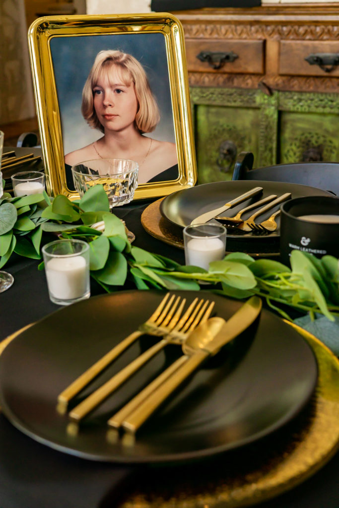 A details shot of the black and gold wedding dinner table with a framed portrait of the bride's late sister on the table. Photo by Gabby Jockers Photography. Garden of the Gods wedding, High point wedding, Colorado intimate wedding, Colorado elopement ideas, elopement inspiration, elopement ideas, Colorado elopement photographer, intimate wedding photography, Rocky Mountain national park wedding, rocky mountains, intimate wedding, September wedding, mountain ceremony view, red rocks wedding