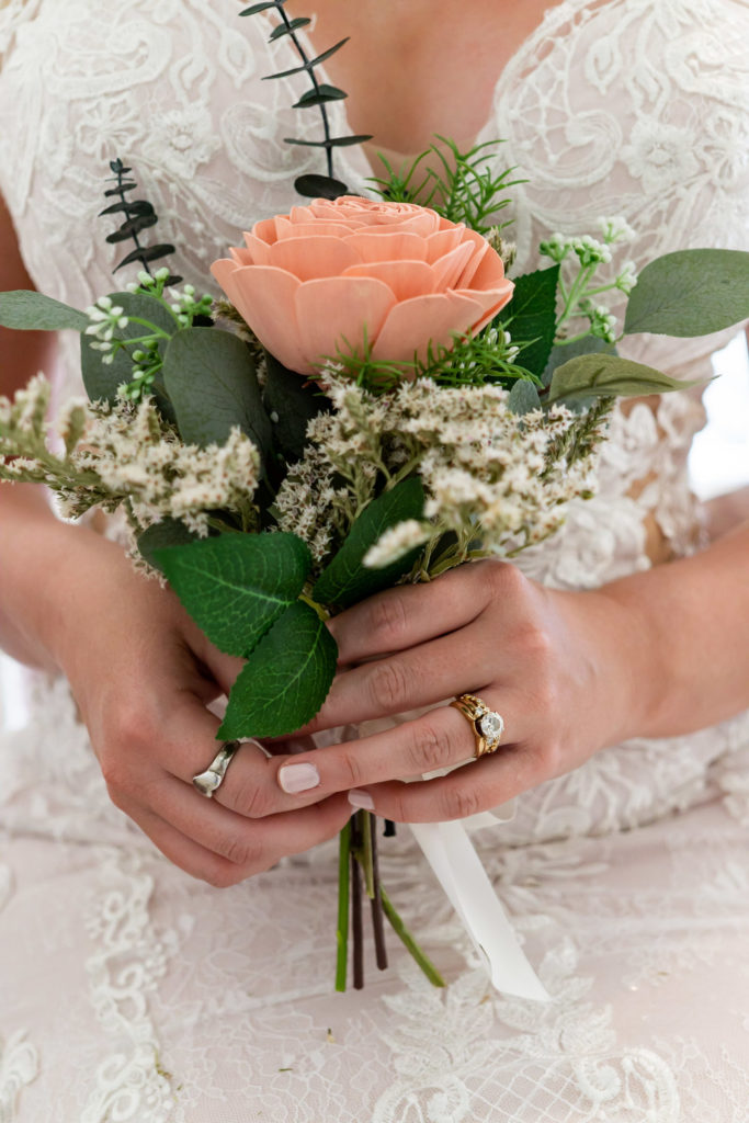 A close up details shot of the bride holding a small wood bouquet with salmon colored flowers , an antique gold engagement ring, and an heirloom ring. Photo by Gabby Jockers Photography. Garden of the Gods wedding, High point wedding, Colorado intimate wedding, Colorado elopement ideas, elopement inspiration, elopement ideas, Colorado elopement photographer, intimate wedding photography, Rocky Mountain national park wedding, rocky mountains, intimate wedding, September wedding, mountain ceremony view, red rocks wedding