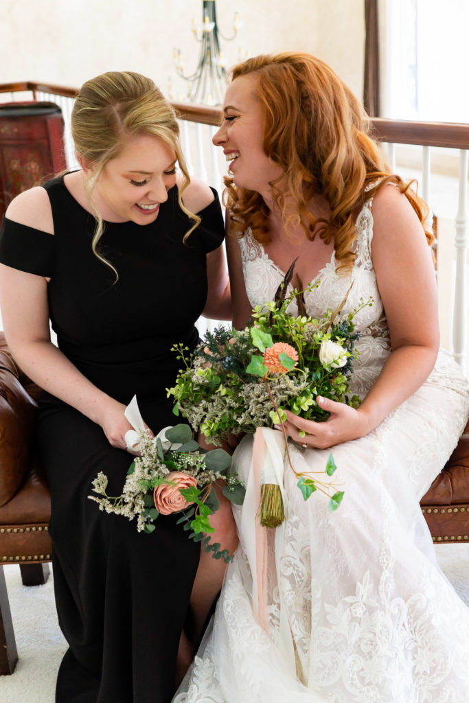 A bride and bridesmaid holding their bouquets while laughing and having fun while getting ready. Photo by Gabby Jockers Photography. Garden of the Gods wedding, High point wedding, Colorado intimate wedding, Colorado elopement ideas, elopement inspiration, elopement ideas, Colorado elopement photographer, intimate wedding photography, Rocky Mountain national park wedding, rocky mountains, intimate wedding, September wedding, mountain ceremony view, red rocks wedding