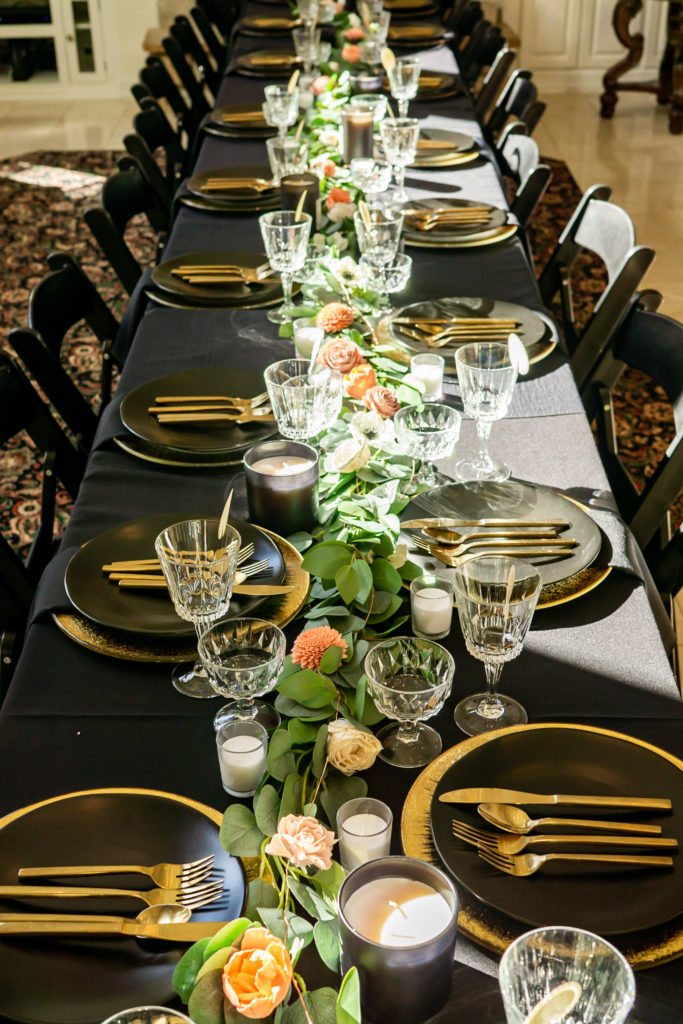 Black and gold wedding table details - a long black table set with gold charges, gold silverware, black plates, and a green garland with salmon wood flowers. Photo by Gabby Jockers Photography. Garden of the Gods wedding, High point wedding, Colorado intimate wedding, Colorado elopement ideas, elopement inspiration, elopement ideas, Colorado elopement photographer, intimate wedding photography, Rocky Mountain national park wedding, rocky mountains, intimate wedding, September wedding, mountain ceremony view, red rocks wedding