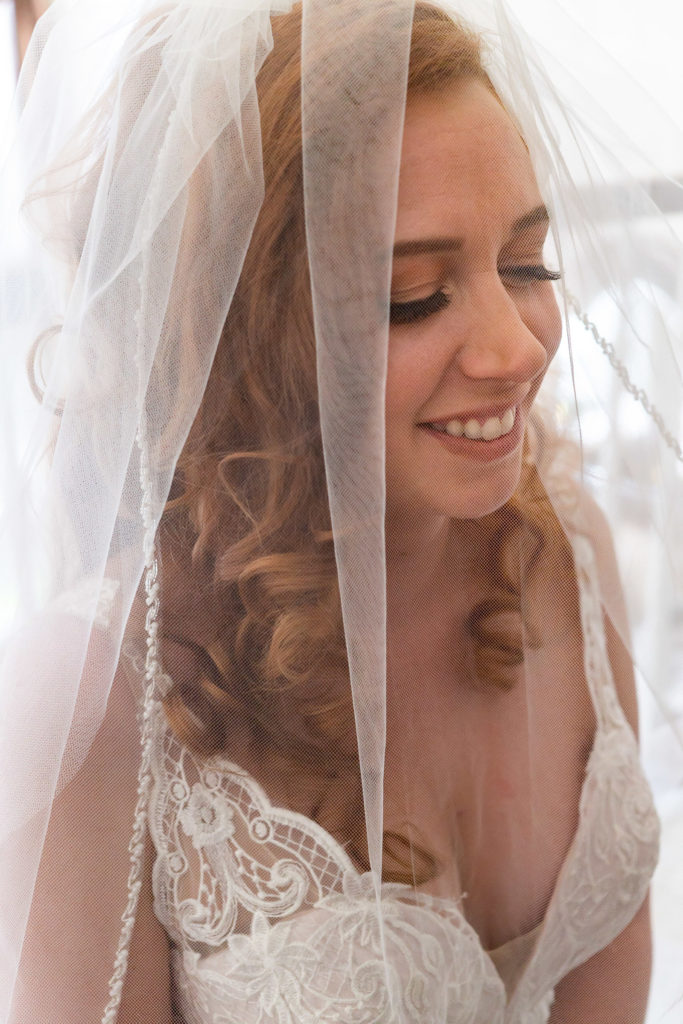 A bride smiling under her veil while wearing a deep v neck lace wedding dress. Photo by Gabby Jockers Photography. Garden of the Gods wedding, High point wedding, Colorado intimate wedding, Colorado elopement ideas, elopement inspiration, elopement ideas, Colorado elopement photographer, intimate wedding photography, Rocky Mountain national park wedding, rocky mountains, intimate wedding, September wedding, mountain ceremony view, red rocks wedding