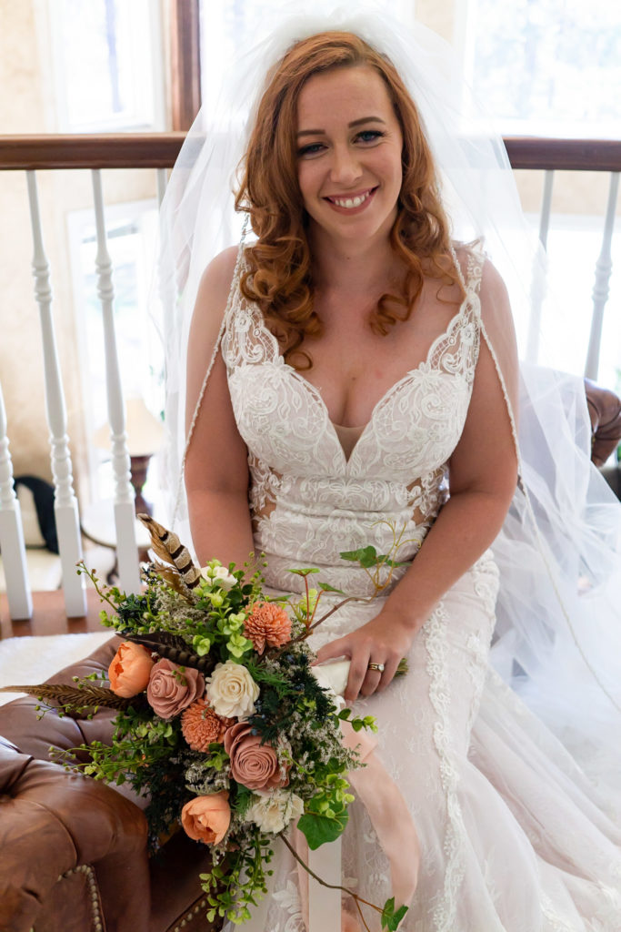 A bride smiling huge while wearing a v neck lace wedding dress and holding her salmon wood bouquet. Photo by Gabby Jockers Photography. Garden of the Gods wedding, High point wedding, Colorado intimate wedding, Colorado elopement ideas, elopement inspiration, elopement ideas, Colorado elopement photographer, intimate wedding photography, Rocky Mountain national park wedding, rocky mountains, intimate wedding, September wedding, mountain ceremony view, red rocks wedding