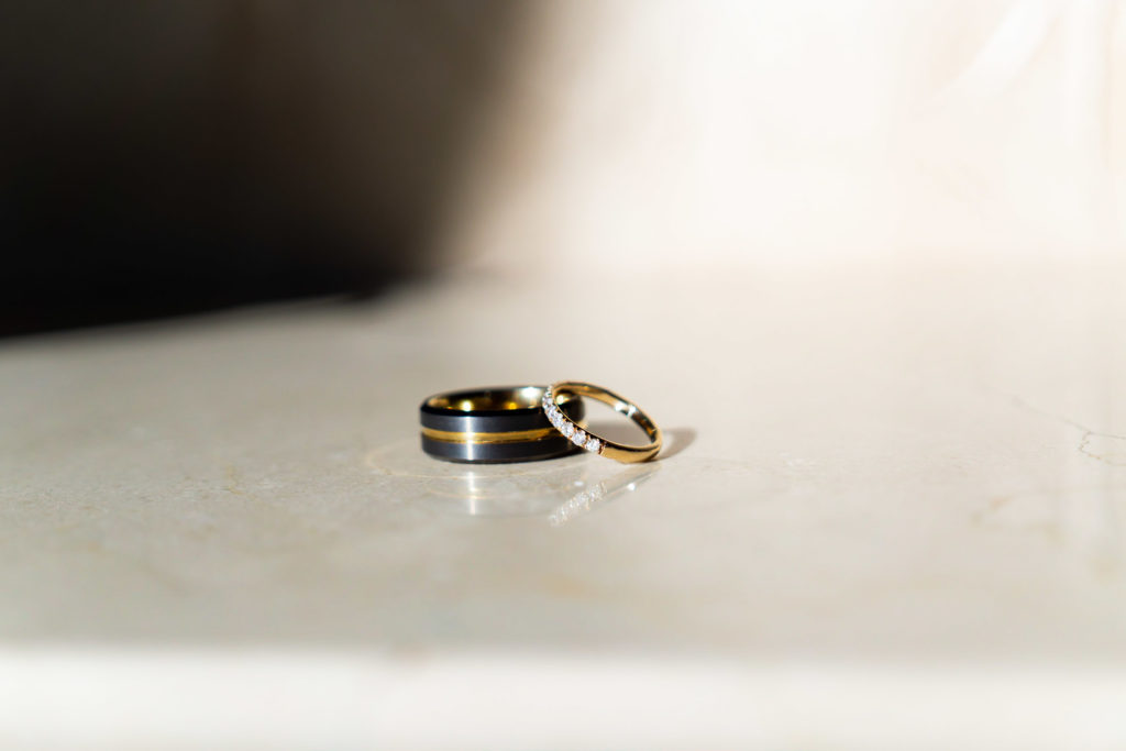 Two wedding rings on a white marble counter. The groom's ring is black with a gold stripe, the bride's ring is gold with inset diamonds. Ring details. Photo by Gabby Jockers Photography. Garden of the Gods wedding, High point wedding, Colorado intimate wedding, Colorado elopement ideas, elopement inspiration, elopement ideas, Colorado elopement photographer, intimate wedding photography, Rocky Mountain national park wedding, rocky mountains, intimate wedding, September wedding, mountain ceremony view, red rocks wedding