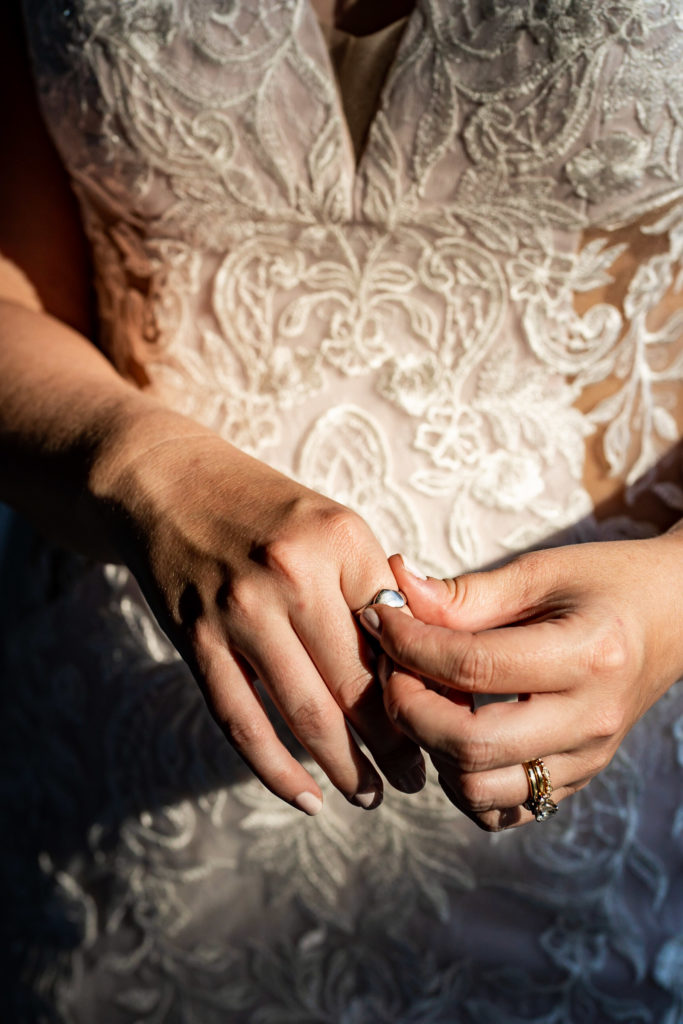A bride wearing a deep V neck lace wedding dress adjusting a cherished family ring on her hand. Photo by Gabby Jockers Photography. Garden of the Gods wedding, High point wedding, Colorado intimate wedding, Colorado elopement ideas, elopement inspiration, elopement ideas, Colorado elopement photographer, intimate wedding photography, Rocky Mountain national park wedding, rocky mountains, intimate wedding, September wedding, mountain ceremony view, red rocks wedding