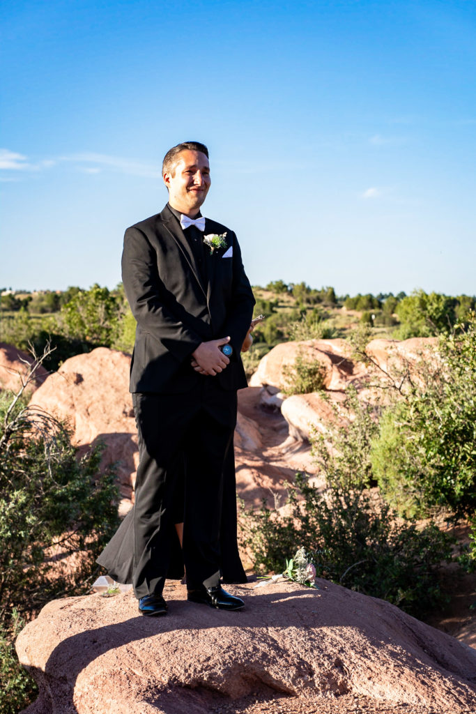 A groom stands in a black tux smiling as he sees his bride in her dress for the first time down the aisle. Photo by Gabby Jockers Photography. Garden of the Gods wedding, High point wedding, Colorado intimate wedding, Colorado elopement ideas, elopement inspiration, elopement ideas, Colorado elopement photographer, intimate wedding photography, Rocky Mountain national park wedding, rocky mountains, intimate wedding, September wedding, mountain ceremony view, red rocks wedding