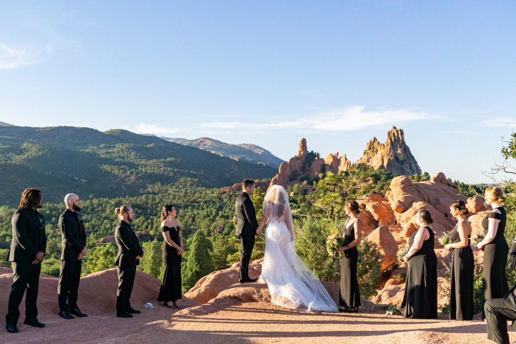 An intimate wedding ceremony at High Point in Garden of the Gods. The bride and groom are surrounded by a bridal party wearing all black against the red rocks. Photo by Gabby Jockers Photography. Garden of the Gods wedding, High point wedding, Colorado intimate wedding, Colorado elopement ideas, elopement inspiration, elopement ideas, Colorado elopement photographer, intimate wedding photography, Rocky Mountain national park wedding, rocky mountains, intimate wedding, September wedding, mountain ceremony view, red rocks wedding