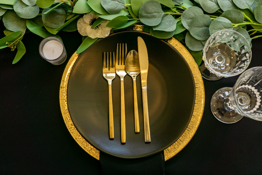 A details shot of the black and gold wedding colors dinner table with a green garland, crystal glasses, gold chargers, black plates, and gold silverware. Photo by Gabby Jockers Photography. Garden of the Gods wedding, High point wedding, Colorado intimate wedding, Colorado elopement ideas, elopement inspiration, elopement ideas, Colorado elopement photographer, intimate wedding photography, Rocky Mountain national park wedding, rocky mountains, intimate wedding, September wedding, mountain ceremony view, red rocks wedding
