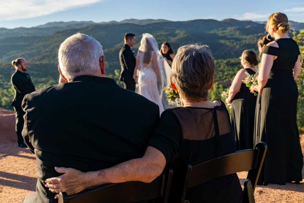 A view of a wedding ceremony at High Point in garden of the gods, from over the shoulders of the in laws. Photo by Gabby Jockers Photography. Garden of the Gods wedding, High point wedding, Colorado intimate wedding, Colorado elopement ideas, elopement inspiration, elopement ideas, Colorado elopement photographer, intimate wedding photography, Rocky Mountain national park wedding, rocky mountains, intimate wedding, September wedding, mountain ceremony view, red rocks wedding