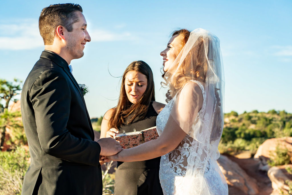 A bride in groom, hand in hand during their wedding ceremony at High Point. They're standing hand in hand in front of their officiant. Photo by Gabby Jockers Photography. Garden of the Gods wedding, High point wedding, Colorado intimate wedding, Colorado elopement ideas, elopement inspiration, elopement ideas, Colorado elopement photographer, intimate wedding photography, Rocky Mountain national park wedding, rocky mountains, intimate wedding, September wedding, mountain ceremony view, red rocks wedding