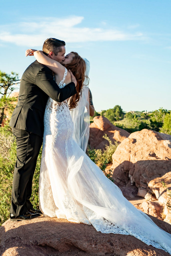 A bride and groom embracing during their first kiss after their wedding ceremony at High Point in garden of the gods. Photo by Gabby Jockers Photography. Garden of the Gods wedding, High point wedding, Colorado intimate wedding, Colorado elopement ideas, elopement inspiration, elopement ideas, Colorado elopement photographer, intimate wedding photography, Rocky Mountain national park wedding, rocky mountains, intimate wedding, September wedding, mountain ceremony view, red rocks wedding