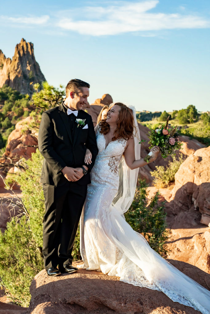 A bride and groom cheering after their wedding ceremony at High Point in garden of the gods. Photo by Gabby Jockers Photography. Garden of the Gods wedding, High point wedding, Colorado intimate wedding, Colorado elopement ideas, elopement inspiration, elopement ideas, Colorado elopement photographer, intimate wedding photography, Rocky Mountain national park wedding, rocky mountains, intimate wedding, September wedding, mountain ceremony view, red rocks wedding