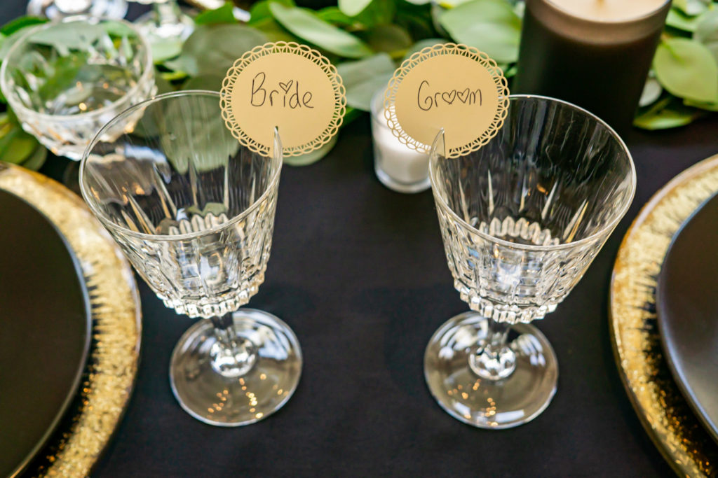 A details shot of the black and gold theme wedding table with matching bride and groom crystal glasses. Photo by Gabby Jockers Photography. Garden of the Gods wedding, High point wedding, Colorado intimate wedding, Colorado elopement ideas, elopement inspiration, elopement ideas, Colorado elopement photographer, intimate wedding photography, Rocky Mountain national park wedding, rocky mountains, intimate wedding, September wedding, mountain ceremony view, red rocks wedding