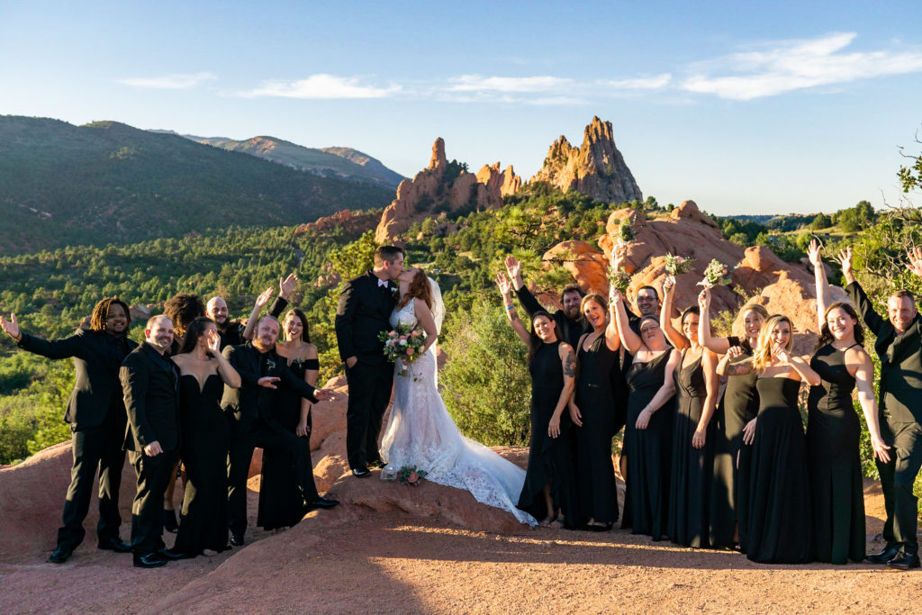 A bride and groom kissing at High Point after their ceremony with the bridal party, all in black, cheering around them. Photo by Gabby Jockers Photography. Garden of the Gods wedding, High point wedding, Colorado intimate wedding, Colorado elopement ideas, elopement inspiration, elopement ideas, Colorado elopement photographer, intimate wedding photography, Rocky Mountain national park wedding, rocky mountains, intimate wedding, September wedding, mountain ceremony view, red rocks wedding