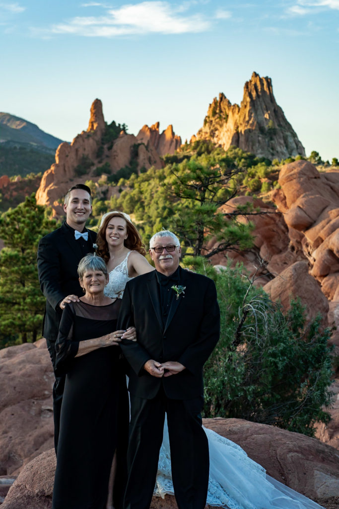 A family photo with the bride, groom, and her parents after their wedding ceremony at Garden of the Gods. Photo by Gabby Jockers Photography. Garden of the Gods wedding, High point wedding, Colorado intimate wedding, Colorado elopement ideas, elopement inspiration, elopement ideas, Colorado elopement photographer, intimate wedding photography, Rocky Mountain national park wedding, rocky mountains, intimate wedding, September wedding, mountain ceremony view, red rocks wedding