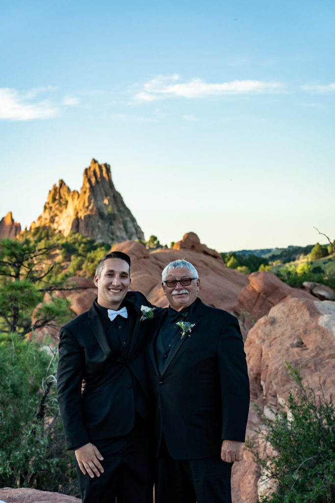 A bride and his father in law embracing in front of the red rock formations of Garden of the Gods. Photo by Gabby Jockers Photography. Garden of the Gods wedding, High point wedding, Colorado intimate wedding, Colorado elopement ideas, elopement inspiration, elopement ideas, Colorado elopement photographer, intimate wedding photography, Rocky Mountain national park wedding, rocky mountains, intimate wedding, September wedding, mountain ceremony view, red rocks wedding