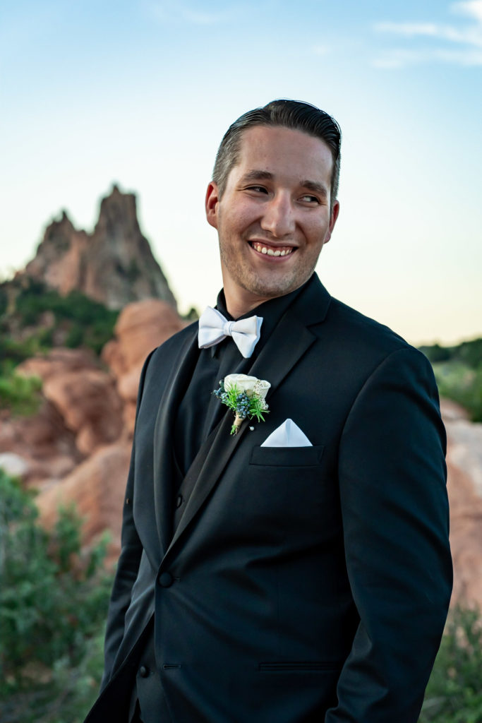 A groom in an all-black tux and white bowtie smiling in front of the red rock formations of Garden of the Gods. Photo by Gabby Jockers Photography. Garden of the Gods wedding, High point wedding, Colorado intimate wedding, Colorado elopement ideas, elopement inspiration, elopement ideas, Colorado elopement photographer, intimate wedding photography, Rocky Mountain national park wedding, rocky mountains, intimate wedding, September wedding, mountain ceremony view, red rocks wedding
