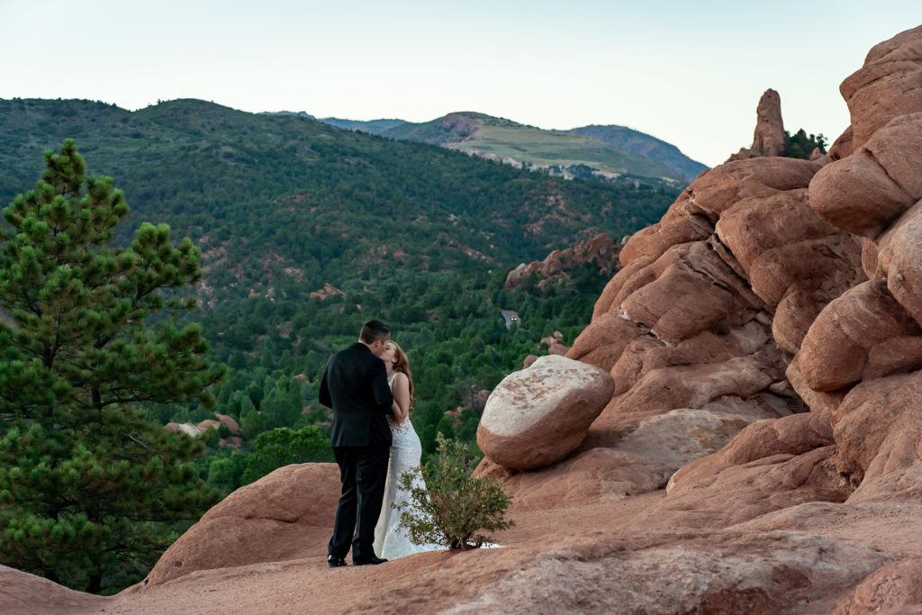 A bride and groom kissing in front of a green mountain view and red rock formations. The bride is wearing a backless lace dress with a long train. Photo by Gabby Jockers Photography. Garden of the Gods wedding, High point wedding, Colorado intimate wedding, Colorado elopement ideas, elopement inspiration, elopement ideas, Colorado elopement photographer, intimate wedding photography, Rocky Mountain national park wedding, rocky mountains, intimate wedding, September wedding, mountain ceremony view, red rocks wedding