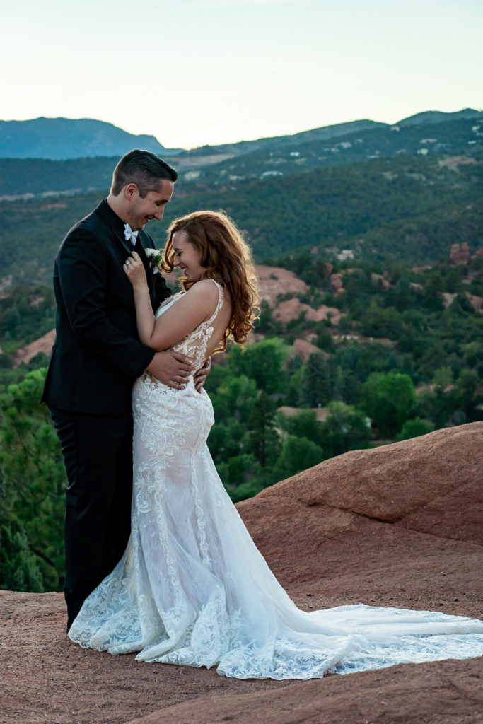 A bride and groom laughing and embracing in front of a green mountain view. The bride is wearing a backless lace dress with a long train. Photo by Gabby Jockers Photography. Garden of the Gods wedding, High point wedding, Colorado intimate wedding, Colorado elopement ideas, elopement inspiration, elopement ideas, Colorado elopement photographer, intimate wedding photography, Rocky Mountain national park wedding, rocky mountains, intimate wedding, September wedding, mountain ceremony view, red rocks wedding