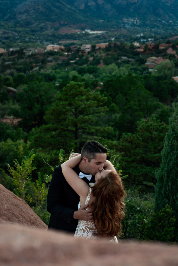 A bride and groom with arms around each other kissing in front of a wide view of trees. Photo by Gabby Jockers Photography. Garden of the Gods wedding, High point wedding, Colorado intimate wedding, Colorado elopement ideas, elopement inspiration, elopement ideas, Colorado elopement photographer, intimate wedding photography, Rocky Mountain national park wedding, rocky mountains, intimate wedding, September wedding, mountain ceremony view, red rocks wedding