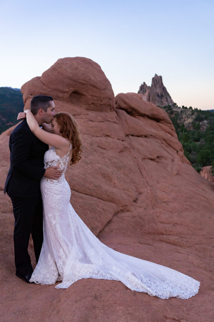 A bride and grooms with their arms around each other, standing in front of the red rock formations of Garden of the Gods. Photo by Gabby Jockers Photography. Garden of the Gods wedding, High point wedding, Colorado intimate wedding, Colorado elopement ideas, elopement inspiration, elopement ideas, Colorado elopement photographer, intimate wedding photography, Rocky Mountain national park wedding, rocky mountains, intimate wedding, September wedding, mountain ceremony view, red rocks wedding