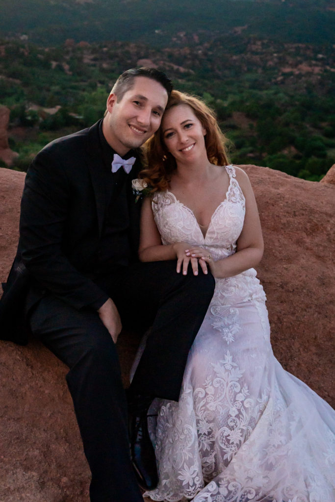 A bride and groom sit on the red rock formations of Garden of the Gods while smiling at the camera. Photo by Gabby Jockers Photography. Garden of the Gods wedding, High point wedding, Colorado intimate wedding, Colorado elopement ideas, elopement inspiration, elopement ideas, Colorado elopement photographer, intimate wedding photography, Rocky Mountain national park wedding, rocky mountains, intimate wedding, September wedding, mountain ceremony view, red rocks wedding