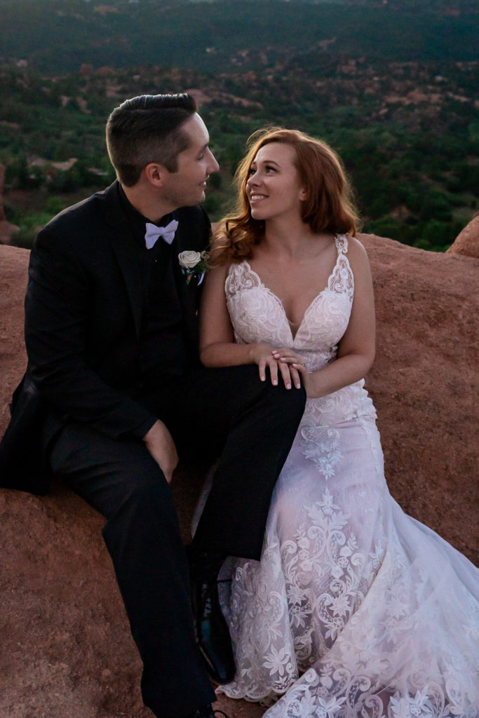 A bride and groom sit on the red rock formations of Garden of the Gods while staring deeply in each others eyes. Photo by Gabby Jockers Photography. Garden of the Gods wedding, High point wedding, Colorado intimate wedding, Colorado elopement ideas, elopement inspiration, elopement ideas, Colorado elopement photographer, intimate wedding photography, Rocky Mountain national park wedding, rocky mountains, intimate wedding, September wedding, mountain ceremony view, red rocks wedding