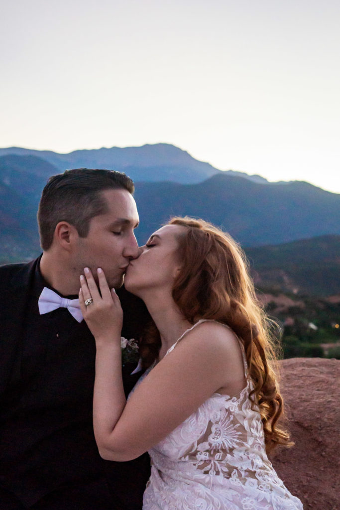 A bride holding her groom on the jaw as they kiss in front of Pike's Peak at High Point. Photo by Gabby Jockers Photography. Garden of the Gods wedding, High point wedding, Colorado intimate wedding, Colorado elopement ideas, elopement inspiration, elopement ideas, Colorado elopement photographer, intimate wedding photography, Rocky Mountain national park wedding, rocky mountains, intimate wedding, September wedding, mountain ceremony view, red rocks wedding