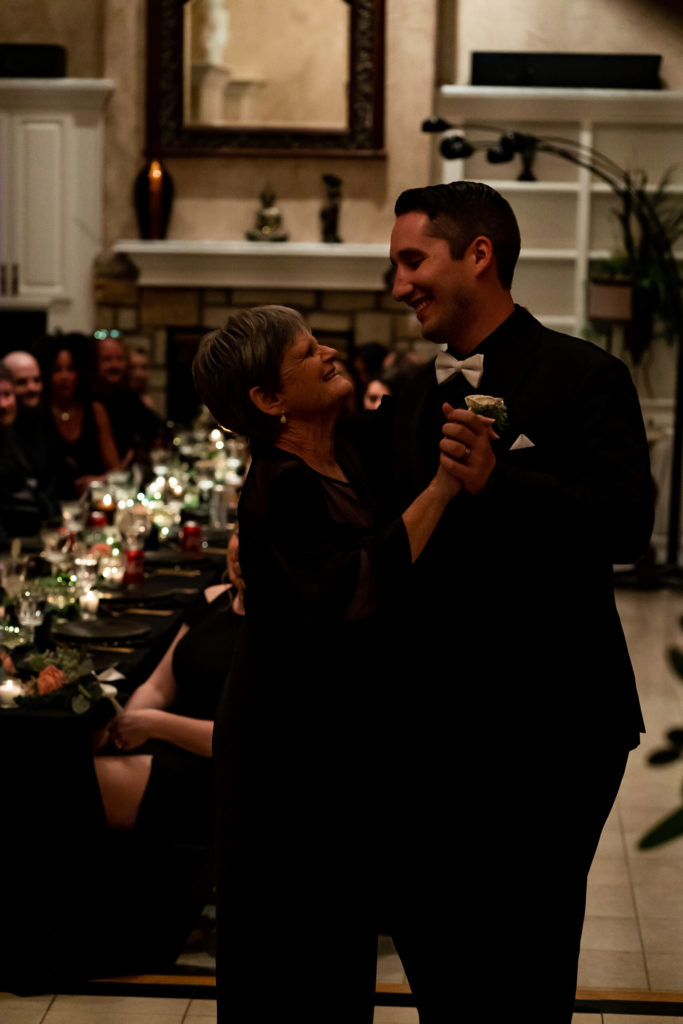 Groom and mother of the bride, all wearing black, doing a mother-son dance in front of the guests at a long black table. Photo by Gabby Jockers Photography. Garden of the Gods wedding, High point wedding, Colorado intimate wedding, Colorado elopement ideas, elopement inspiration, elopement ideas, Colorado elopement photographer, intimate wedding photography, Rocky Mountain national park wedding, rocky mountains, intimate wedding, September wedding, mountain ceremony view, red rocks wedding
