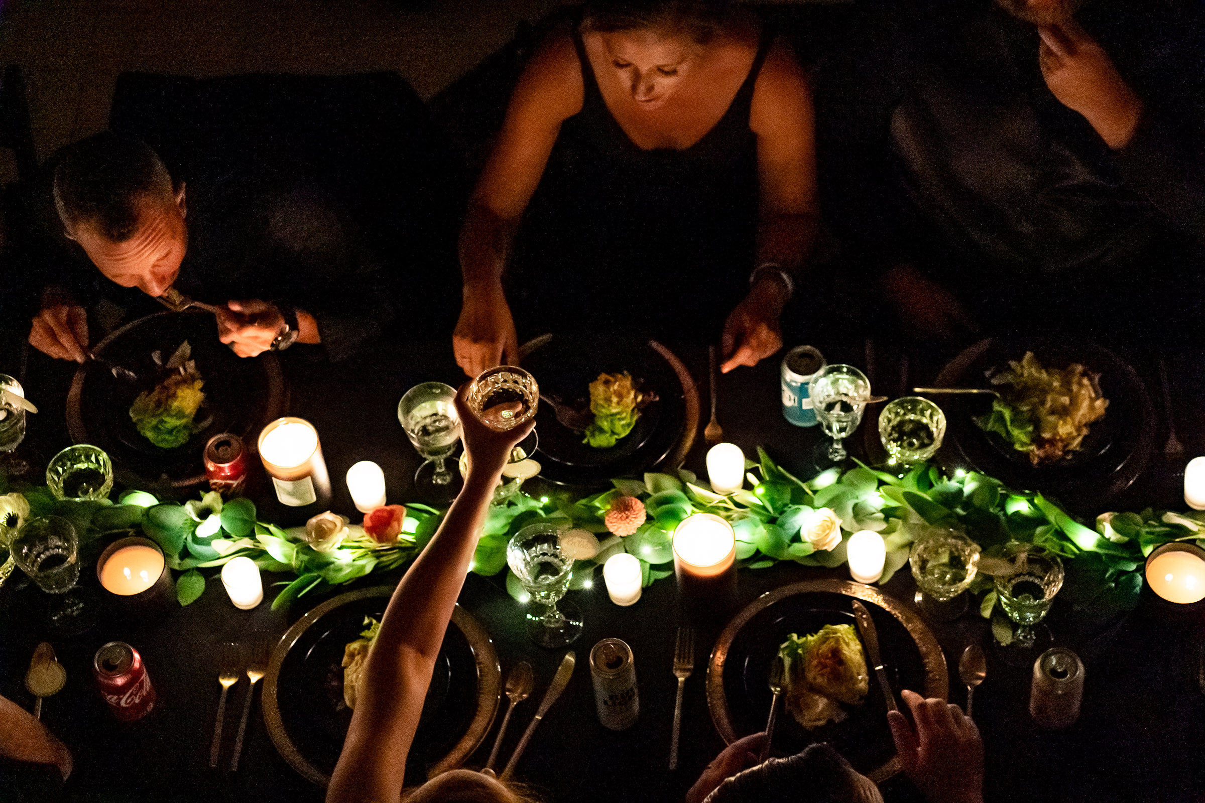 The guests of a wedding sitting at a long black dinner table with candles, gold runners, black plates, g old silverware, green garland, red flowers. Photo by Gabby Jockers Photography. Garden of the Gods wedding, High point wedding, Colorado intimate wedding, Colorado elopement ideas, elopement inspiration, elopement ideas, Colorado elopement photographer, intimate wedding photography, Rocky Mountain national park wedding, rocky mountains, intimate wedding, September wedding, mountain ceremony view, red rocks wedding