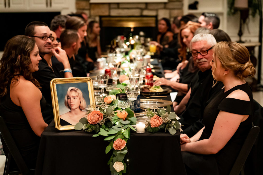 The guests of a wedding sitting at a long black dinner table with a photo memorial to the bride's late sister at the head of the table. Photo by Gabby Jockers Photography. Garden of the Gods wedding, High point wedding, Colorado intimate wedding, Colorado elopement ideas, elopement inspiration, elopement ideas, Colorado elopement photographer, intimate wedding photography, Rocky Mountain national park wedding, rocky mountains, intimate wedding, September wedding, mountain ceremony view, red rocks wedding