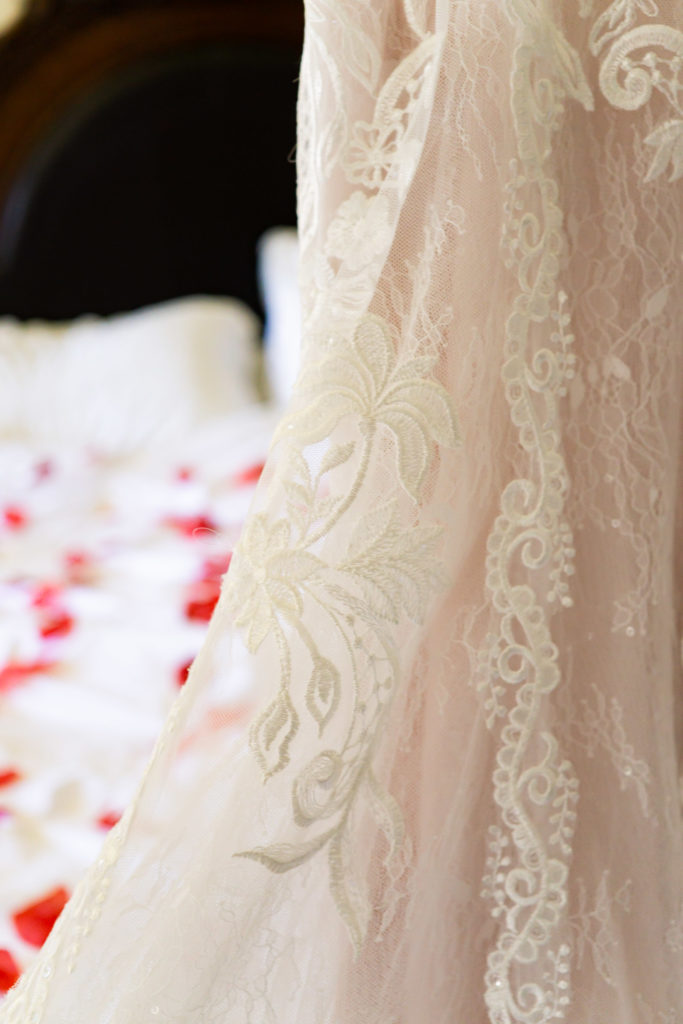 A details shot of a lace wedding dress in front of a bed covered in rose petals. Photo by Gabby Jockers Photography. Garden of the Gods wedding, High point wedding, Colorado intimate wedding, Colorado elopement ideas, elopement inspiration, elopement ideas, Colorado elopement photographer, intimate wedding photography, Rocky Mountain national park wedding, rocky mountains, intimate wedding, September wedding, mountain ceremony view, red rocks wedding