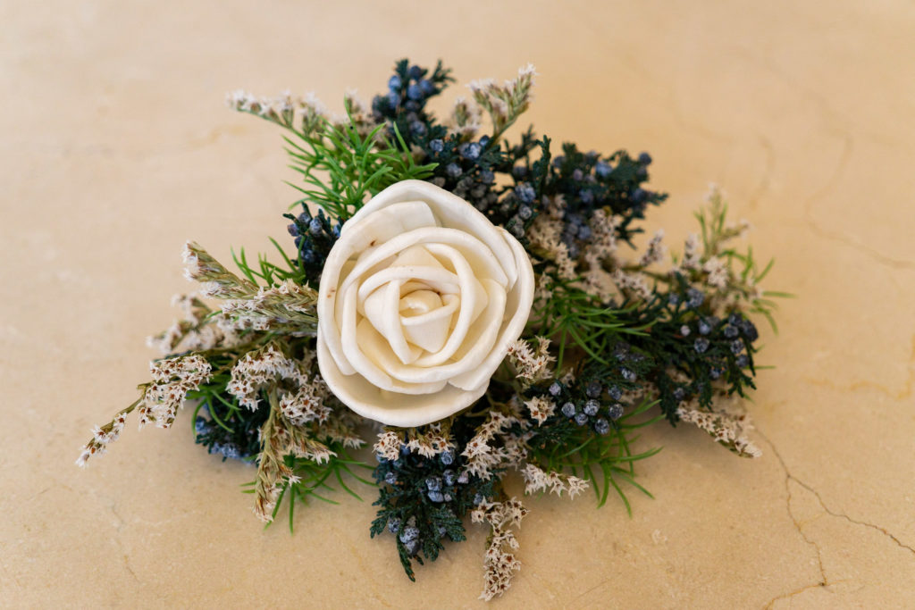 A white sola wood boutonniere against white marble. Photo by Gabby Jockers Photography. Garden of the Gods wedding, High point wedding, Colorado intimate wedding, Colorado elopement ideas, elopement inspiration, elopement ideas, Colorado elopement photographer, intimate wedding photography, Rocky Mountain national park wedding, rocky mountains, intimate wedding, September wedding, mountain ceremony view, red rocks wedding
