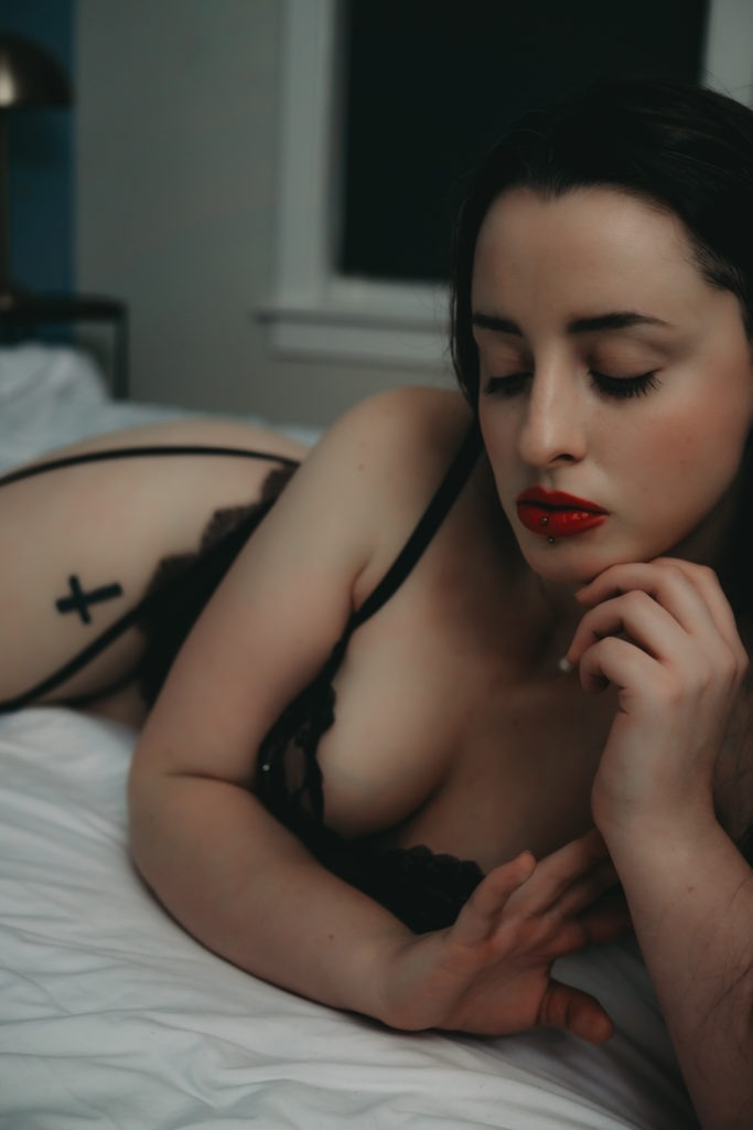 Beautiful lady with dark red lipstick and piercing on lips is lying on the bed sensually wearing black lacy lingerie, Boudoir photoshoot, boudoir photography, boudoir inspiration, boudoir photography ideas, sensual photography, Denver boudoir photographer, golden boudoir photographer, colorado boudoir photographer, self love, love language, words of affirmation, physical touch, quality time, acts of service, touch, self care, affirmations, best lingerie store for boudoir photography session